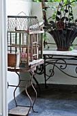 Birdcage on rusty stand on balcony