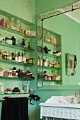 Toiletries on glass shelves in niche next to framed mirror in green bathroom