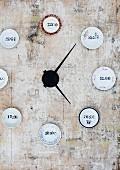 Wanduhr-Unikat mit gestempelten Uhrzeiten auf kleinen Tellern
