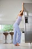 Woman standing opening refrigerator door