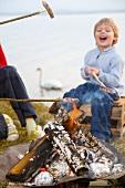 Mädchen und Junge braten Würstchen über dem Lagerfeuer