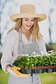 Frau hält Tablett mit Frühlingsblumen