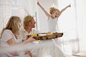 Schwangere Frau und Familie beim Frühstück im Bett