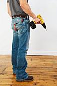 Mann in Jeans mit Akkuschrauber in der Hand