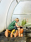 Woman planting flower in green house