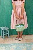 Mädchen in festlichem Kleid hält Korb mit gefärbten Ostereiern