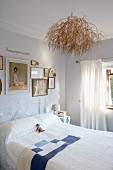 Bright bedroom with bundle of twigs on ceiling lamp above bed with white, delicate metal frame below framed pictures on wall