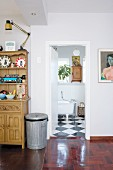 Metal dustbin next to dresser in hallway and view though open door into bathroom with black and white chequered floor