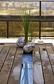 Wooden platform on a terrace decorated with aquatic plants and stones