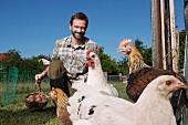 Man feeding chickens outdoors