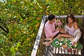 Couple eating breakfast outdoors smiling.