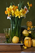 Vase of daffodils with Golden Delicious and Temptation apples