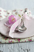 Cutlery with a bell flower and place card on a pink plate