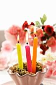 Brennende Kerzen vor Rosenstrauss