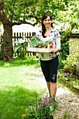 Woman with crate of vegetables in garden