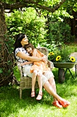 Mother and daughter cuddling in garden chair
