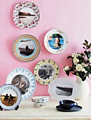 Holiday photos on patterned china plates on pink-painted wall