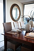 Set table and wicker chairs in dining room; round, framed mirror on wall