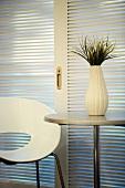 White designer chair next to white vase on round table in front of sliding blinds