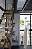 Eine Stahltreppe mit Holzstufen im Fabrikstil führt vom Wohnzimmer mit großer Fensterfront auf die Galerie