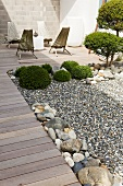 Garden chairs on a landscaped terrace with boxwood topiaries in a gravel bed