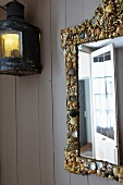 Wall mirror with a shell frame and antique wall lantern on a wood paneled wall