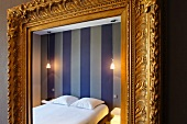 Detail of a baroque wall mirror with a gold frame in a bedroom