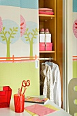 Pastel colored tree stencils on the half open sliding door of a closet in a little girl's room