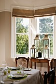 Set table and collection of lanterns in dining room bay window