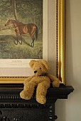Beige teddy bear sitting slumped on dark mantelpiece in front of gilt-framed picture of horse in countryside leaning on wall
