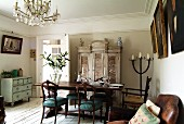 Living-dining room with crystal chandelier, antique dining table and elegant upholstered chairs on rustic, white-painted wooden floor and shabby-chic furniture
