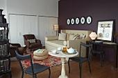 Bistrotisch im Antikstil und tiefes Polstersofa im Wohnzimmer mit Einbauschränken und violetter Wand