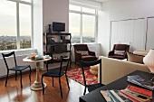Bistrotisch im Antikstil und Polstermöbel im Wohnzimmer mit großen Fenstern und Blick über die Stadt