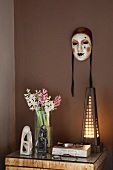 Hand painted Venetian masks on a brown wall above a night stand