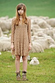Young girl standing in a pasture in front of sheep