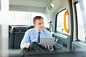 A business man with a tablet PC sitting in the back of a car