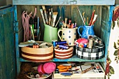 Blue wooden cupboard with paintbrushes, pens and sewing materials in patterned boxes and jugs