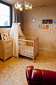 Cot with canopy in nursery clad in chipboard