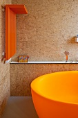 Corner of a bathroom with an orange, heated towel rail on a wall made of particle board and a partially visible bath tub