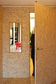 Open door in room clad with chipboard made of large wood chips