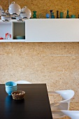 Black dining table and white chairs in front of white overhead cupboard on chipboard-clad wall