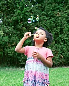 Dark haired girl blowing soap bubbles