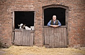 A farmer and a calf looking over barn doors