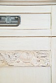 Detail of cabinet with drawer and carving on white wooden door