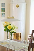 Dining area - art deco pendant lamp above vase of yellow flowers on table opposite white tiled corner fireplace