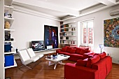 Modern seating area with two comfortable, red sofas and white upholstered armchairs around modern coffee table