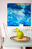Green apples on decorative china plates in front of oil painting in shades of blue