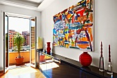 Abstract painting above glossy black sideboard and open balcony door with view of city