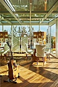 Lounge in conservatory with guitar and white upholstered chairs around glass table