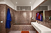 Modern designer bathroom with continuous mosaic tiling and transom window of glass bricks